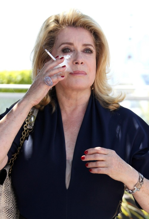 Legendary actress Catherine Deneuve enjoys a cigarette at the photocall for the French film